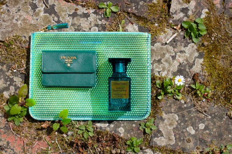 iridescent pouch Prada cardholder and bottle of fragrance on old bricks