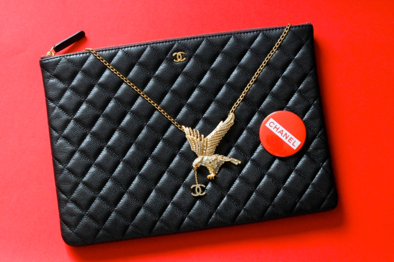 black quilted Chanel clutch and gold eagle necklace on a red background