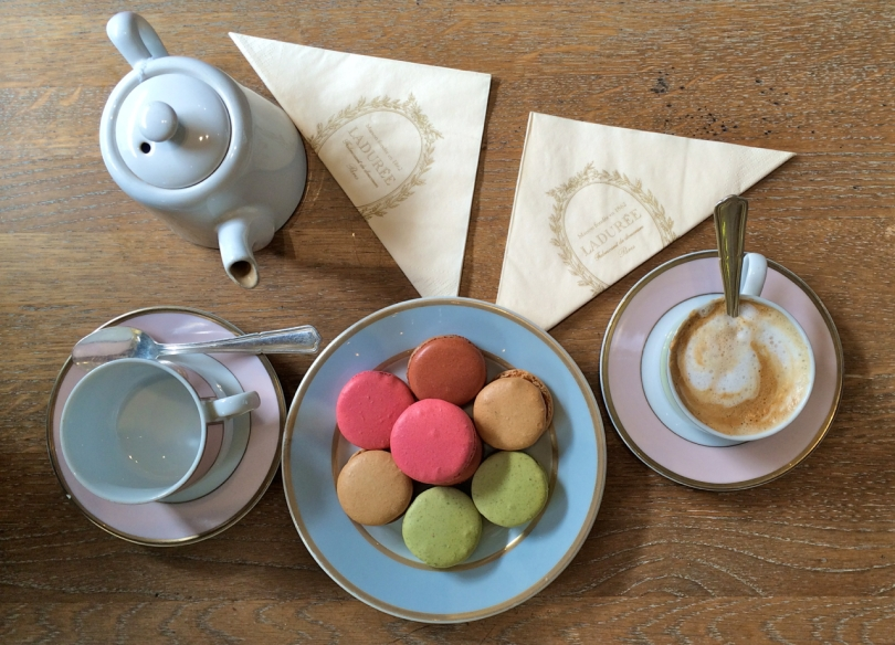 wooden table with colourful macaroons coffee and teapot