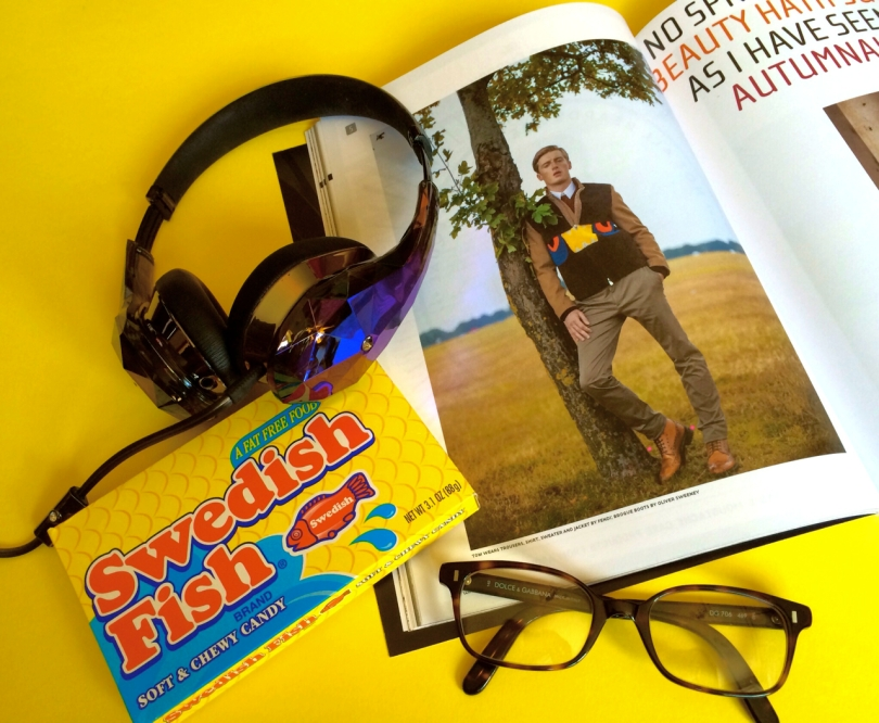 open fashion magazine with swedish fish candy reading glasses and shiny headphones