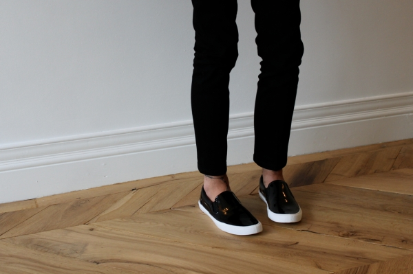 close up of black patent skate shoes against antique chevron wooden floor
