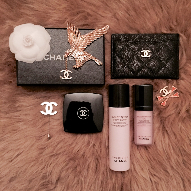 Chanel jewellery and cosmetics flatlay on a sheepskin rug