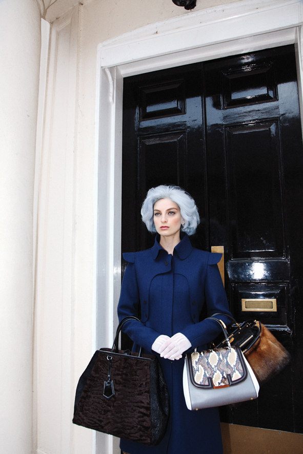 lady fendi against black front door wearing navy coat and pastel blue hair