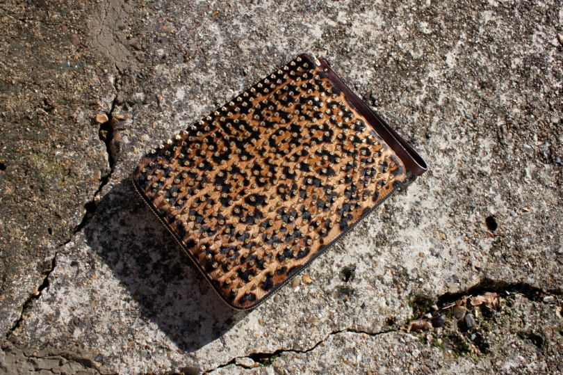 Louboutin studded leopard iPad case on concrete