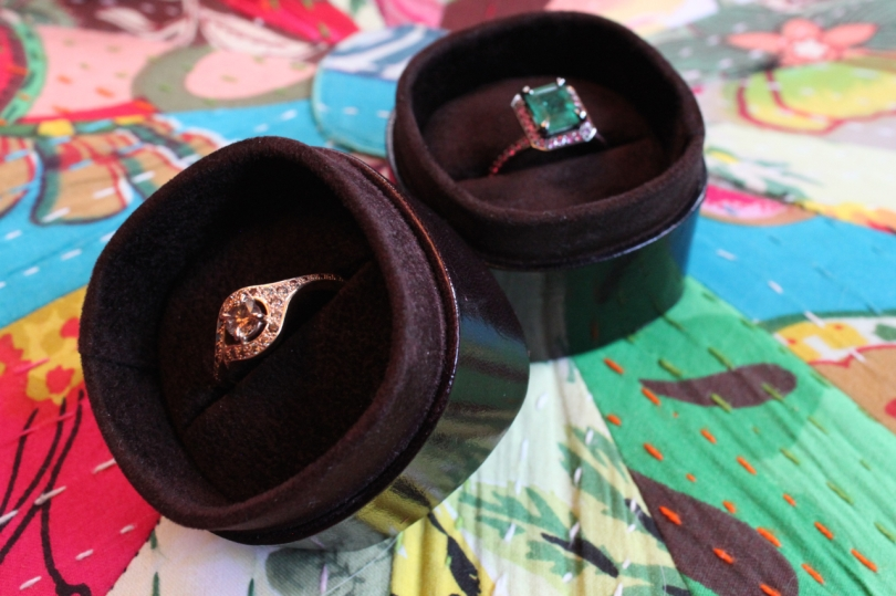 two bespoke rings from Baroque Brighton in their boxes against a colourful cushion