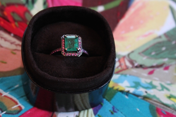bespoke black gold emerald ring with ruby halo in brown leather box on a colourful cushion