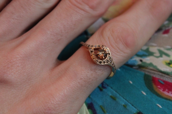 close up of hand wearing bespoke cognac diamond ring set in pink gold