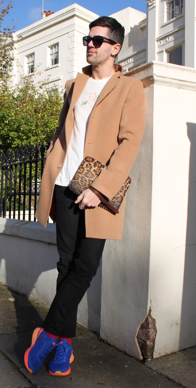 leaning against pillar wearing a camel cashmere coat and sunglasses