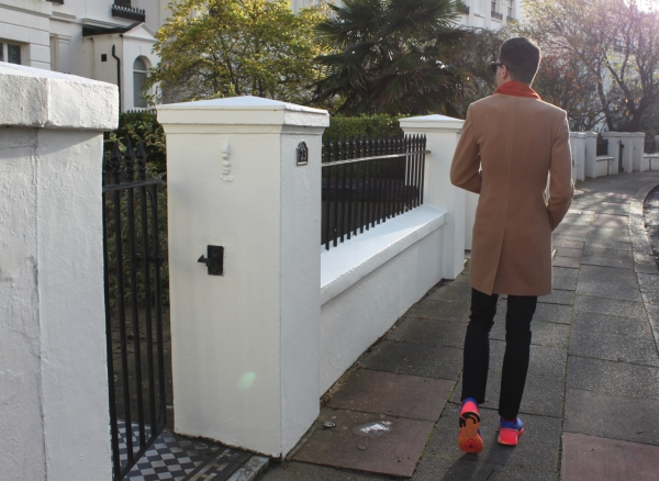 walking away down a brighton crescent in a camel coat with orange under collar