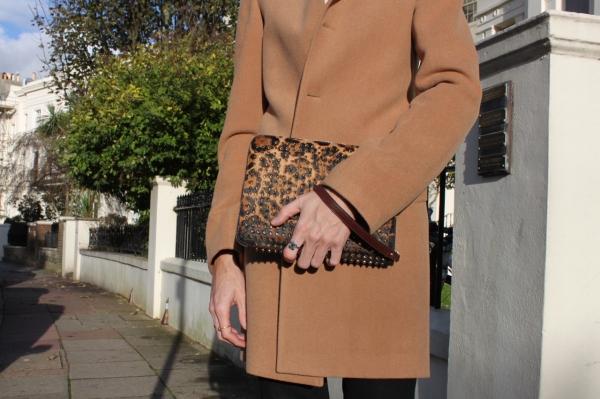 close up shot of leopard print pony hair iPad case and camel coat