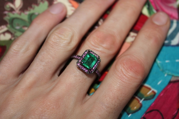 wearing bespoke large emerald ring set in blackened white gold surrounded by pink rubies