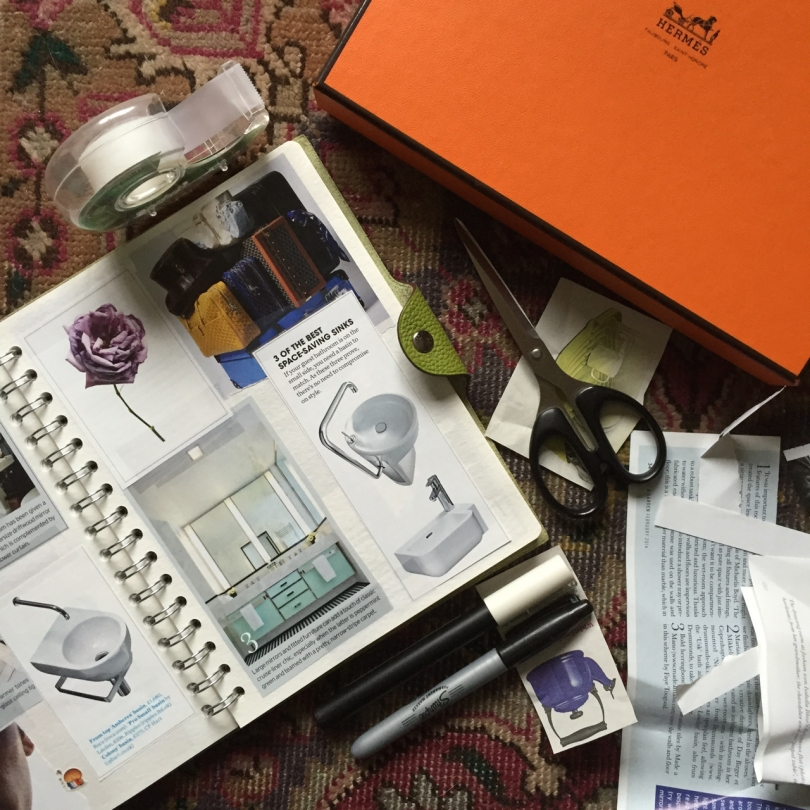 flatly of an hermes scrapbook surrounded by sticky tape scissors bits of paper and pens