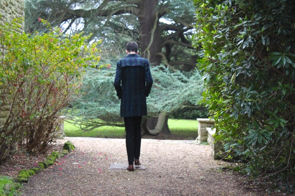 walking away by a country house wearing navy and green checked coat