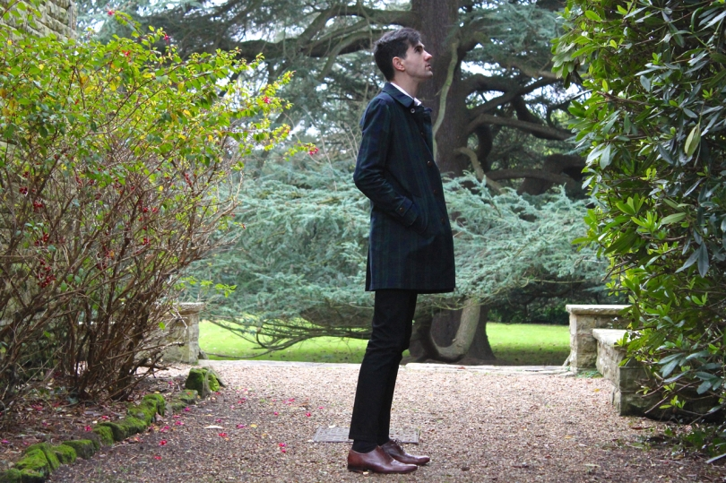stood in the grounds of country house wearing checked coat and black jeans