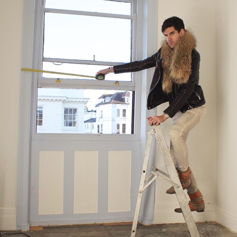 measuring sash window with tape measure wearing balmain