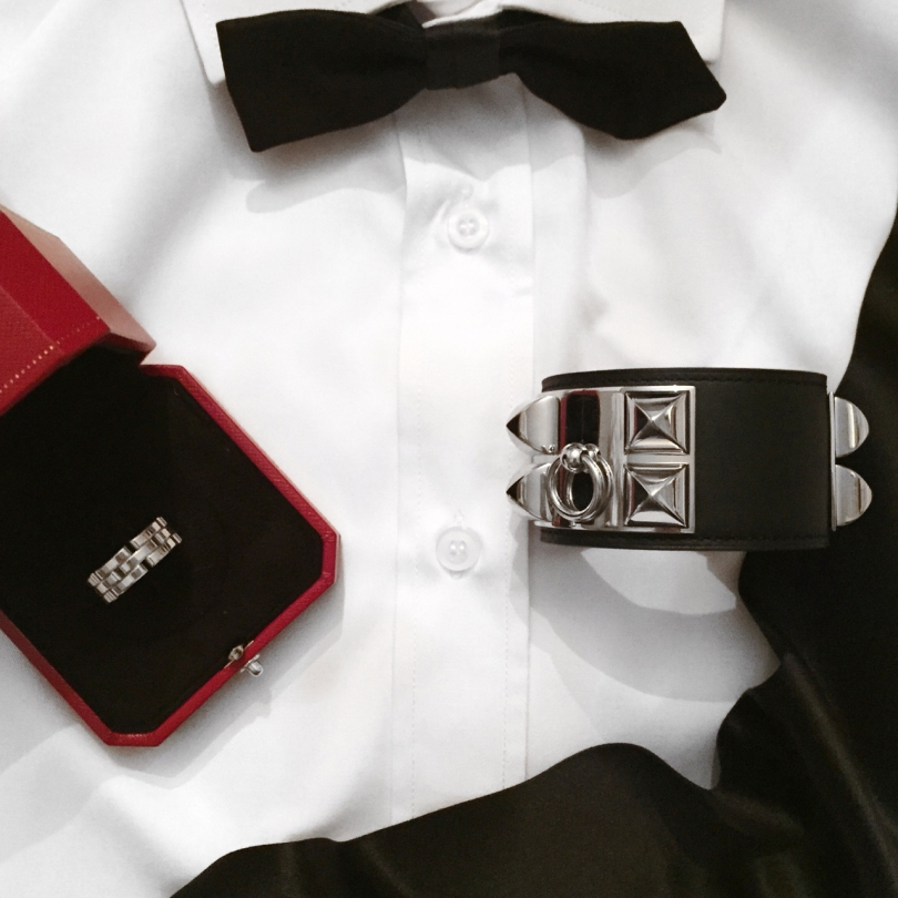 new years eve flatlay of white shirt with cartier ring in box hermes cuff and dior black satin bow tie
