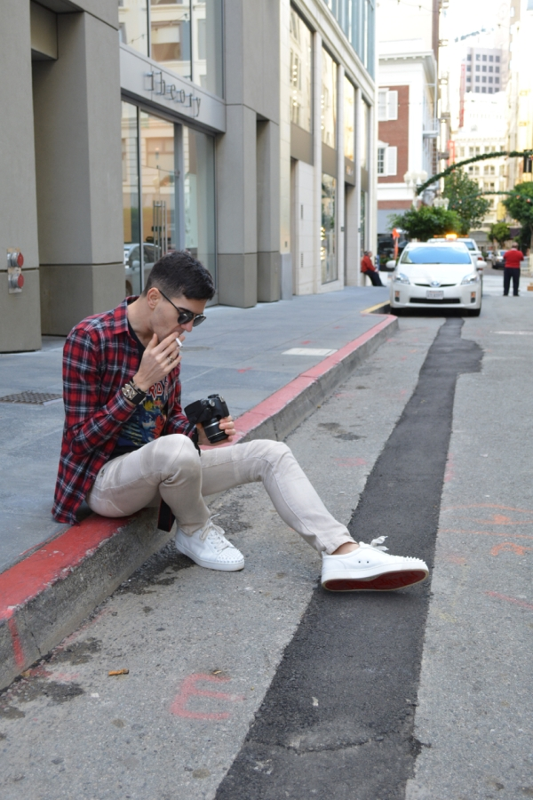 sat on the curb smoking looking at pictures on a camera