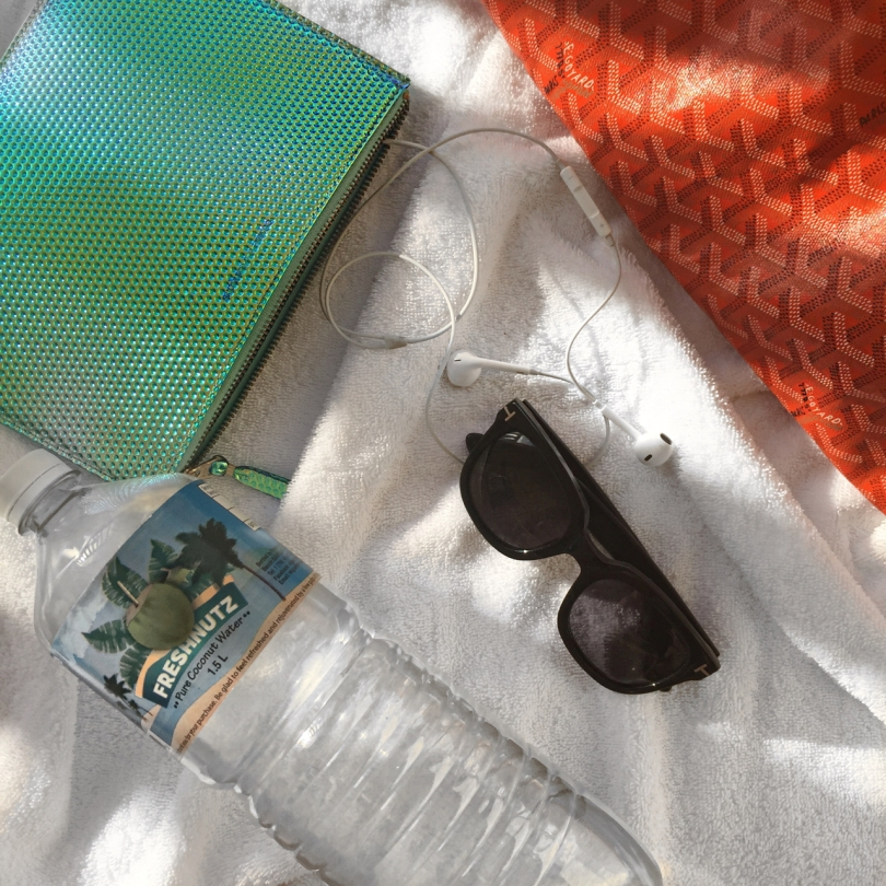 flatlay of beach essentials with orange goyard bag tom ford sunglasses and coconut water