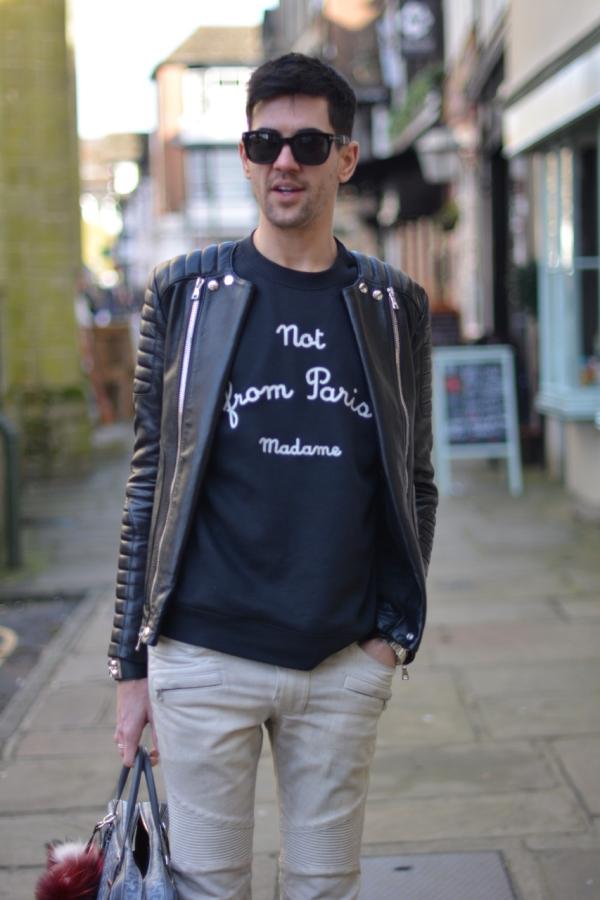 street style shot wearing balmain jacket and jeans role de monsieur sweatshirt and grey goyard bag