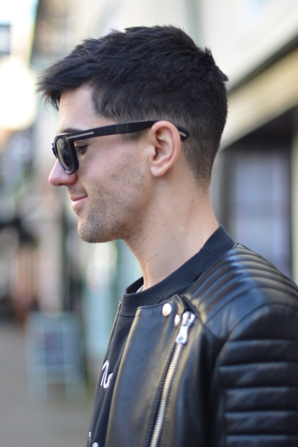 side shot wearing tom ford sunglasses and black leather balmain biker jacket