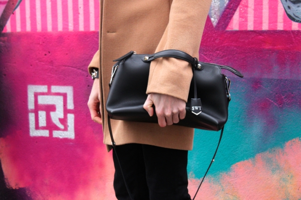 close up of black leather fend by the way bag with graffiti in the background