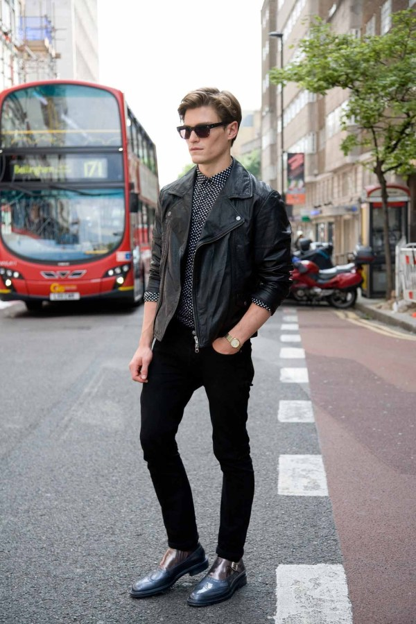 London street style shot of man wearing black outfit with boots