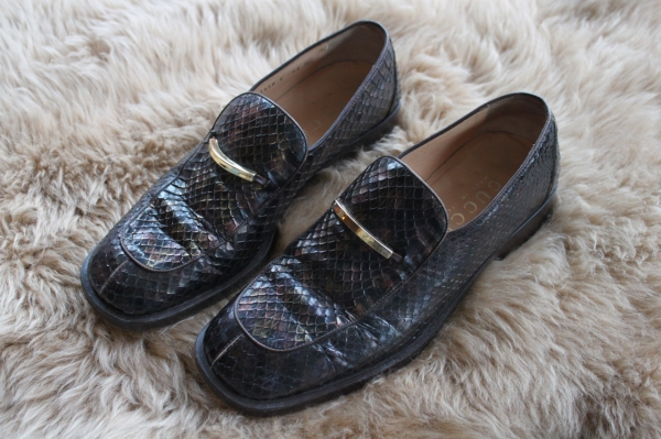 side shot of brown python gucci loafers deigned by tom ford on a sheepskin rug