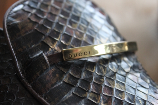 close up of gold bar detail on brown gucci python loafers