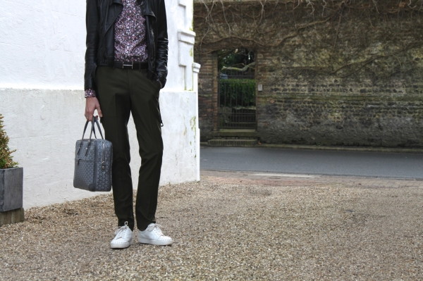 headless photo wearing floral shirt with black biker jacket army green trousers hermes belt and grey goyard bag