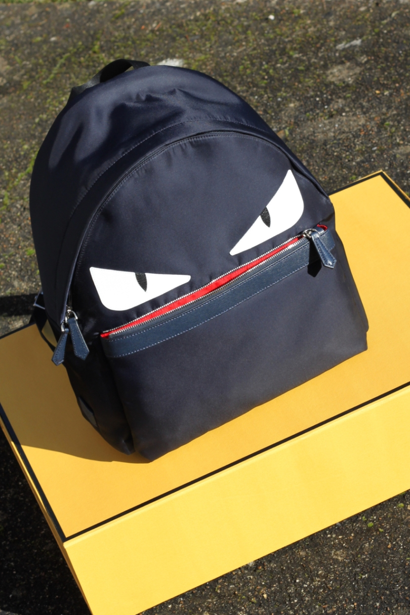 navy Fendi monster backpack with red mouth on a yellow box