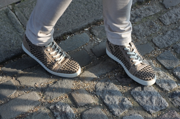 Christian Louboutin Louis Flat Spikes hightop shoes on a cobbled street in Brighton