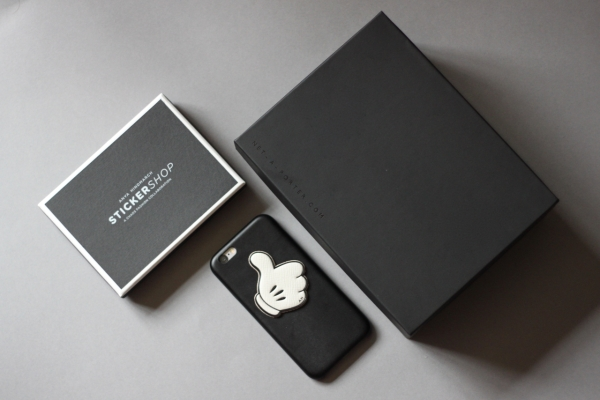 flat lay with Anya Hindmarch thumbs up leather sticker on black iPhone 6 case surrounded by boxes