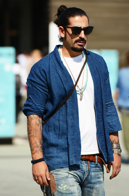 street style shot of man with sunglasses and top knot wearing double denim with a white t shirt