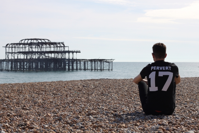 sat looking out at the sea with brighton west pier ruins in shot