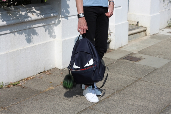 holding Fendi monster backpack in Brighton wearing Adidas Stan Smith sneakers